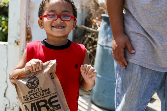 A boy smiles after receiving a packaged meal in San Juan, Puerto Rico, Oct. 12, 2017, from Soldiers assigned to the 3rd Expeditionary Sustainment Command.