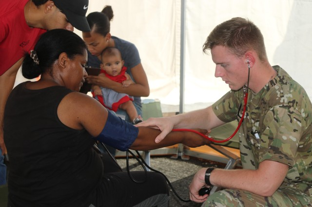 Army Pfc. Leon Good, a medic with the 1st Armored Division, tends to patients near Fajardo, Puerto Rico at the Federal Emergency Management Agency's National Disaster Medical System, a mobile emergency and clinical care facility, Oct. 13, 2017. The medics were seeing up to 150 patients a day.
