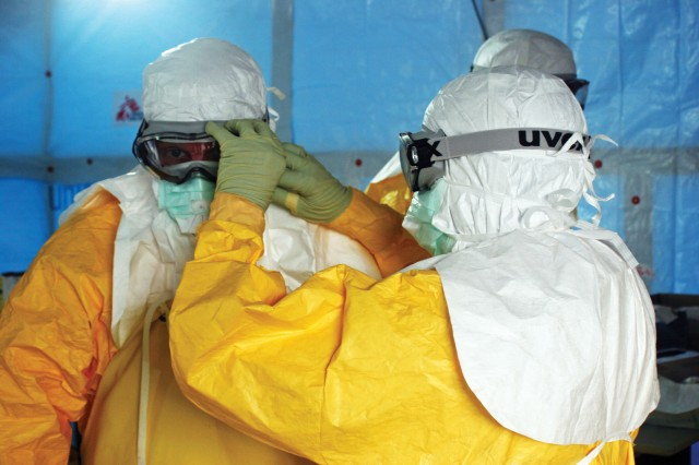 Health care providers adjust personal protective equipment before entering an Ebola treatment unit in Liberia. Ebola spreads through contact with an infected person's bodily fluids, so health care workers are at high risk of infection. Helping host nations implement rigorous protocols for donning and removing personal protective equipment is one key to containing outbreaks, and one line of effort for JPM-MCS in collaboration with WHO and others. (Photo by Athalia Christie, CDC)