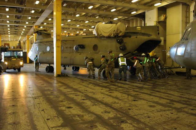 Soldiers push a Chinook helicopter out of its parking place before offloading it at Pearl Harbor on Oct. 10.