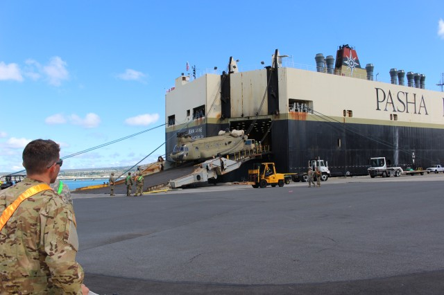 Soldiers and port operators offload a Chinook helicopter from the M/V Jean Anne during discharge operations at Pearl Harbor on Oct. 10.