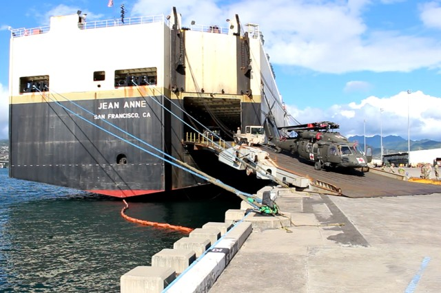 Soldiers and transporters offload a 25th CAB Black Hawk helicopter from the M/V Jean Anne during discharge operations at Pearl Harbor on Oct. 10.