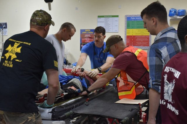 Capt. Nathaniel Turner, physician's assistant, along with medics Spc. Joseph Allen, Sgt. Joshua Serrano and Spc. Ryan Devanna, 86th Combat Support Hospital, prepare to move a patient with a simulated leg fracture to a gurney for transport to a helicopter for medical evacuation during a mass casualty training event held at Camp Buehring, Kuwait, Sept. 23, 2017. The 86th CSH held the MASCAL to assess the readiness of their medics, as well as supporting units including the military police, EMS, and fire fighters, also located at Camp Buehring.