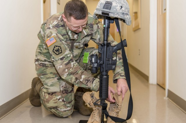 U.S. Army Chaplain Maj. Andrew Shriver adjusts items displayed on the new Portable Memorial Stand at Fort Belvoir Community Hospital