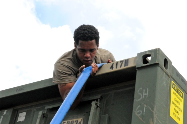 Spc. Dacabeon Fuller, 247th Composite Supply Company, prepares to receive water from a Reverse Osmosis Water Purification Unit at a distribution location near Aguadillas, Puerto Rico, Oct. 16, 2017. The Fort Carson, Colorado soldier volunteered to provide support to the relief efforts in the U.S. Virgin Islands, but when Hurricane Maria devastated Puerto Rico, Fuller continued on to the Island to help the people of Puerto Rico.