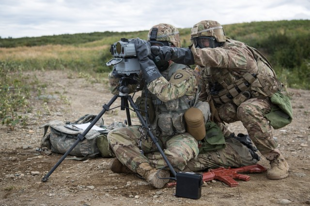 Sgt. Richard Martinez (left) and Spec. Nicholas A. Whelan, Soldiers from Battery D, 2nd Battalion, 8th Field Artillery Regiment, detect, recognize, and identify a target using the Joint Effects Targeting System Target Laser Designation System (JETS-TLDS) while wearing chemical, biological, radiological, nuclear, and enhanced conventional weapons (CBRNE) equipment.
