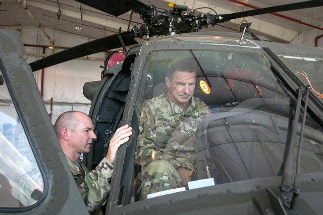 Lt. Col. Andrew Duss, a product manager for Program Executive Office Aviation, explains to Gen. James McConville, the vice chief of staff of the Army, new avionics developments on a UH-60V Blackhawk helicopter during a visit to Redstone Arsenal, Ala., on Aug. 3, 2017.