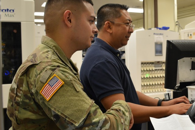Spc. Isaac Coronado (left) and Ed Alfonso (right), certified pharmacy technicians at Tripler Army Medical Center (TAMC) process prescriptions at the TAMC out-patient pharmacy clinic on Oct. 13, 2017.