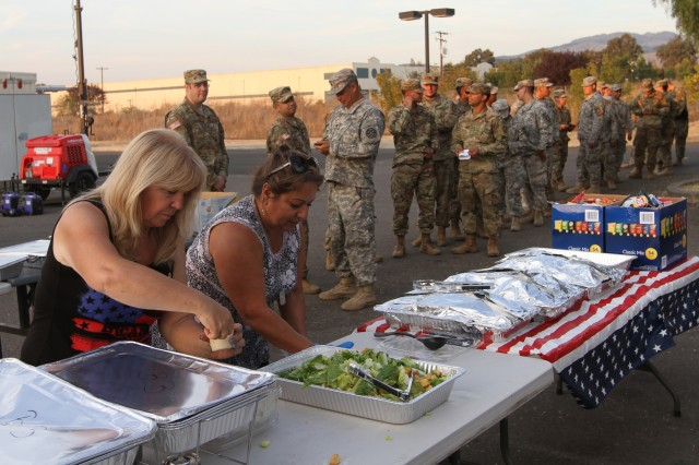 Sindy Biederman and Michelle Marquez, members of American Canyon Troop Support (ACTS), prepare a meal for more than 200 California Army National Guardsmen operating out of the Napa County Airport in Napa, California, during the 2017 Northern California wildfires.