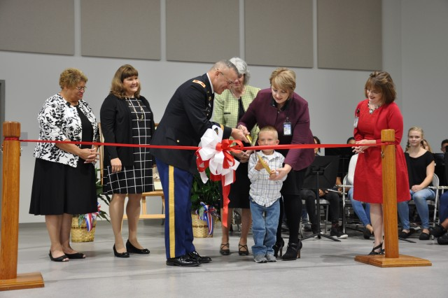 "Second grader Hayden Compton, cuts the ribbon along with Col. Gary ""Eddie"" Gillon Jr., Chief of Staff, 1st Sustainment Command, Fort Knox, Kentucky, and Laura Gibson, principal of Kingsolver Elementary School."