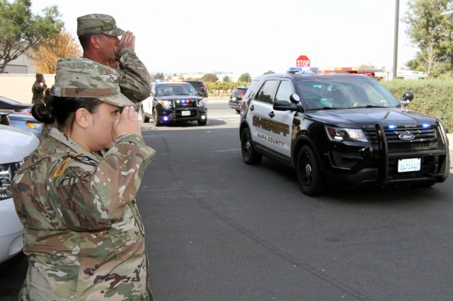 Capt. Antonia Ambriz of Headquarters Detachment, 185th Military Police Battalion, 49th Military Police Brigade, California Army National Guard, salutes with other Cal Guardsmen as vehicles escorting a fallen volunteer fighter enter the Napa County Sheriff's Department in Napa, California, Oct. 16. The salute pays the utmost respect to the deceased, says Col. Robert Paoletti, 49th commander, who stood behind the formation. The volunteer hailed from Missouri and his cause of death is being investigated, per the Sheriff's Office. More than 40 people have died from the recent Northern California wildfires.