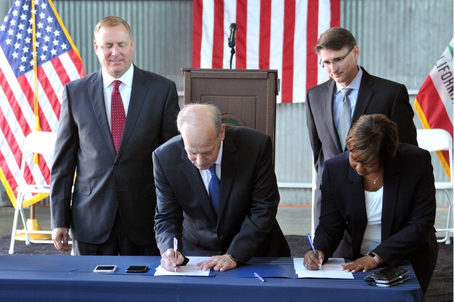 RIVERBANK, California -- Mayor Richard O'Brien (second from left) and Brenda Johnson-Turner (right), Director of Real Estate for the U.S. Army Corps of Engineers, sign the memorandum of agreement that transfers 28 acres of U.S. Army land to the city Oct. 17. At left is Congressman Jeff Denham; Deputy Assistant Secretary of the Army for Installations Paul Cramer is second from right.