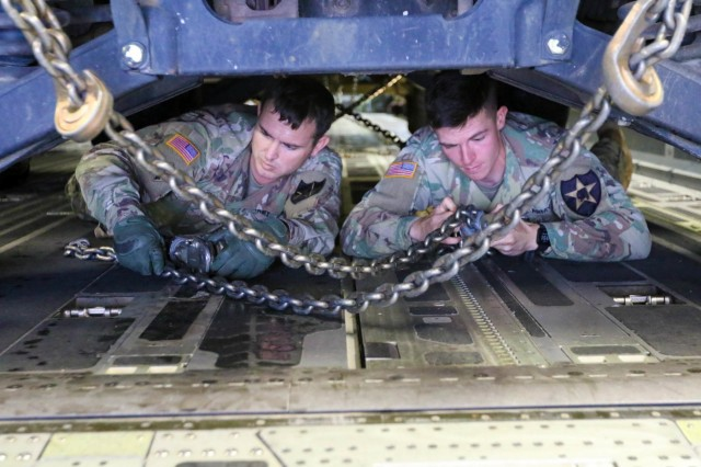 Sgt. Daniel Hudgins, a fire support specialist, and Pfc. Ryan Peterson, a field artillery automated tactical data systems specialist, both with Headquarters and Headquarters Battalion, 2nd Infantry Division Artillery, secure a military vehicle down in a C-17 Globemaster prior to flight at Joint Base Lewis-McChord, Wash. Oct. 18, 2017.