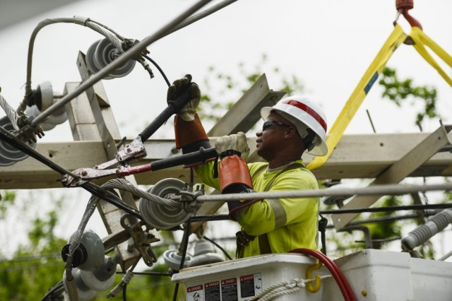 Jitu Whitehead, a lineman from the 249 Engineer Battalion (Prime Power),   repairs a distribution line. Prime Power engineers bring proven power generation capabilities, capable of transmitting electricity over long distances whenever and wherever it is needed.