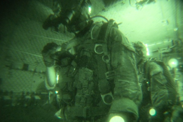 A Special Forces military free fall team with the Parachute Navigation System (PARANAVSYS), prepares to exit an aircraft during a night operation.