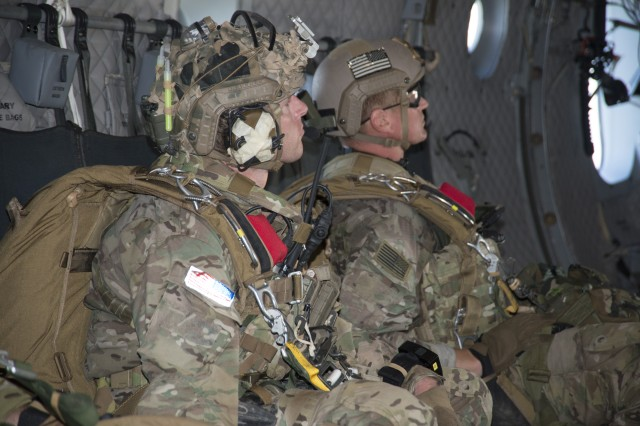 Special Forces Soldiers rigged with the Parachute Navigation System (PARANAVSYS) and combat equipment prepare to jump.