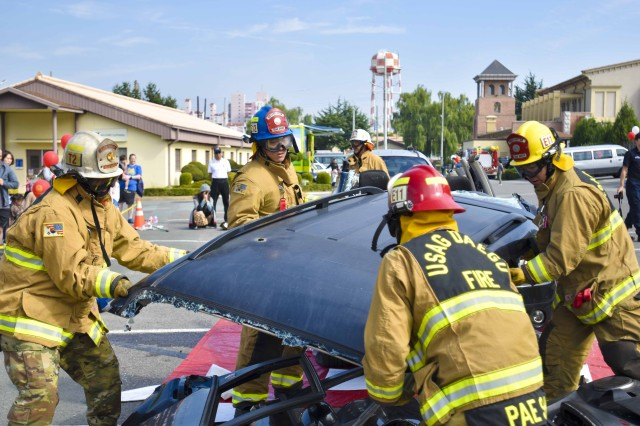 Firefighters from USAG Daegu Fire and Emergency Services tears off the roof from the damaged vehicle while performing vehicle extrication demonstration during the Fire Prevention Open House, Oct. 14, at the Camp Walker Kelly Field. (U.S. Army photo by Pfc. Kim, Bum-joon)