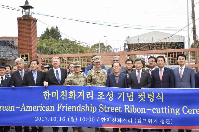 USAG Daegu Commander Col. Robert P. Mann, Command Sgt. Maj. Juan A. Abreu, and the garrison directorates pose in front of the Ribbon-cutting Ceremony banner alongside their Korean local community counterparts. After the ceremony, all the participants took a stroll down the renewed street. (U.S. Army photo by Pfc. Kim, Bum-joon)