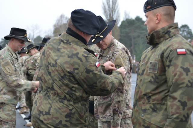 Col. Dariusz Parylak, commander, 10th Armored Cavalry Brigade, 11th Lubuska Armored Cavalry Division, presents a 10th Armored Cavalry Brigade patch to unit commanders from 5th Squadron, 4th Cavalry Regiment, 2nd Armored Brigade Combat Team, 1st Infantry Division, at Red Square in Swietoszow, Poland, Oct. 23. Lt. Col. Dave Maxwell presents the 1st Infantry Division patch to unit commanders from the 10th Armored Cavalry Brigade. The patch exchange occurs during a ceremony that celebrates the partnership and friendship of the two units. The 5th Squadron, 4th Cavalry Regiment, 2nd Armored Brigade Combat Team, is in Europe to support Atlantic Resolve. Atlantic Resolve is a U.S. endeavor to fulfill NATO commitments by rotating U.S. -based units throughout the European theater and training with NATO Allies and partners. (U.S. Army photo by Sgt. Shiloh Capers)