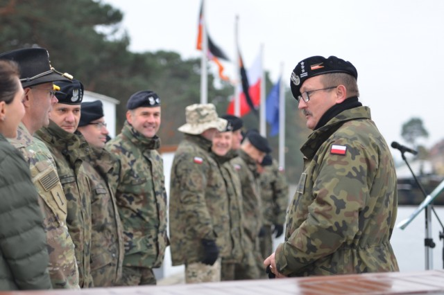 U.S. Army Lt. Col. Dave Maxwell, squadron commander, 5th Squadron, 4th Cavalry Regiment, 2nd Armored Brigade Combat Team, 1st Infantry Division, speaks with Col. Dariusz Parylak, commander, 10th Armored Cavalry Brigade, 11th Lubuska Armored Cavalry Division, during a ceremony for the two units, Red Square in Swietoszow, Poland, Oct. 23. The ceremony celebrates the partnership between the U.S. and Polish forces. The 5th Squadron, 4th Cavalry Regiment, 2nd Armored Brigade Combat Team, is in Europe to support Atlantic Resolve. Atlantic Resolve is a U.S. endeavor to fulfill NATO commitments by rotating U.S. -based units throughout the European theater and training with NATO Allies and partners. (U.S. Army photo by Sgt. Shiloh Capers)