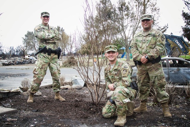 California Army National Guard Soldiers from the 270th Military Police Company, 49th Military Police Brigade, help nurture a tree that was left standing after the Tubbs Fire in Santa Rosa. The house nearby burned to the ground, but residents begged the California Guardsmen who were controlling a nearby traffic point to care for the tree. Residents were not allowed into the affected areas yet.