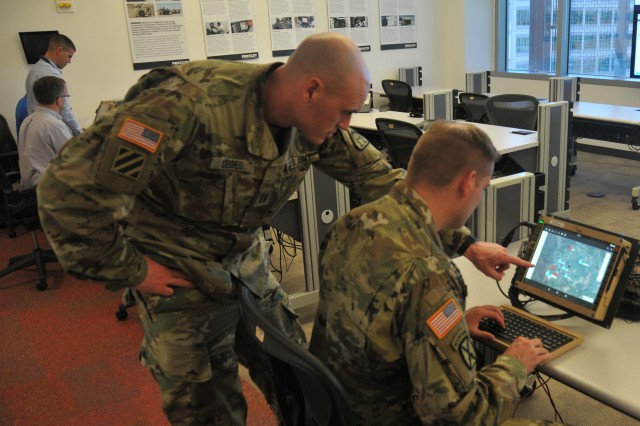 Capt. David Gerdes (standing) and Capt. John (Mack) Turner demonstrate the Command Post Computing Environment prototype at Aberdeen Proving Ground, Maryland, on May 16, 2017.