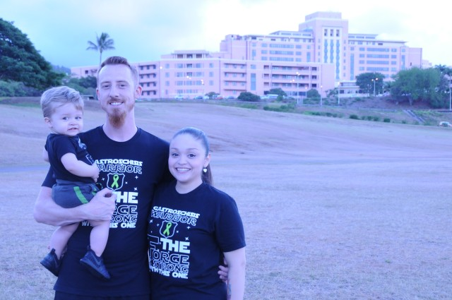 Brandon and Maira Carrier stand with their son, Brandon Jr., in front of Tripler Army Medical Center before Gastroschisis Awareness Day walk/run..