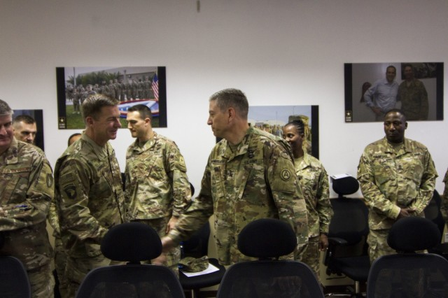 The 36th Army Vice Chief of Staff, Gen. James C. McConville, shakes hands with Col. Gary E. Spearow, Chief of Mobility for U.S. Army Central Command, before a briefing in Camp Arifjan, Kuwait, Oct. 16, 2017. McConville toured facilities and met with key leaders and junior Soldiers during the visit.