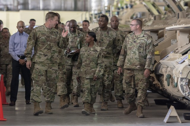 The 36th Vice Chief of Staff of the Army, Gen. James C. McConville, walks with Col. Carmelia Scott-Skillern, commander, 401st Army Field Support Brigade, and other leaders in the 401st AFSB, during a warehouse tour in Camp Arifjan, Kuwait, Oct. 16, 2017. The warehouse contains vehicles that are part of Army Prepositioned Stocks-5, a large stockpile of equipment that allows the Army to rapidly deploy combat units without having to ship their equipment, if needed and ordered by senior leaders. (Photo: Justin Graff, 401st Army Field Support Brigade)