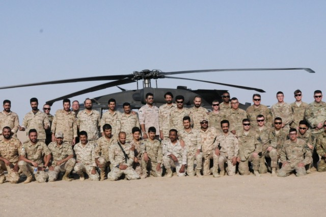 UDARI, Kuwait - Soldiers from the 29th Combat Aviation Brigade's 1-147 Assault Helicopter Battalion, Task Force Wraith, pose with members of the Kuwait Land Forces during training rehearsals for exercise Desert Wall at Camp Buehring, Kuwait, Oct. 4, 2017. Desert Wall consisted of air and ground assault training and tested the interoperability of the Kuwait Soldiers with their U.S. counterparts. (Photo by U.S. Army Staff Sgt. Isolda Reyes)