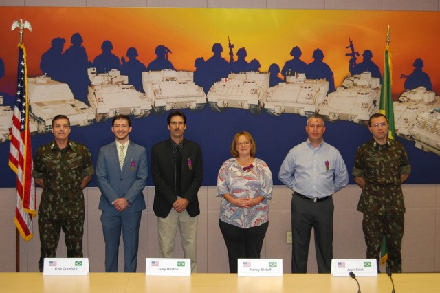 Brig. Gen. Sidnei Prado, Brazilian Army director of materiel, (far left) and Maj. Gen. Miriano Valdoni Eder, Brazilian Army artillery commander, (far right) stand with (left to right) Kyle Crawford, Gary Huston, Nancy Sieloff and Josh Smrt who were presented the Peacemaker Medal for their significant contributions to the Brazilian Army's security assistance program.