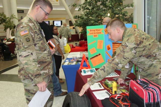 Sgt. William Strickland (right) an orthopedic technician for Medical Department Activity - Alaska,  gives an overview on effective tire treads to Sgt. Thomas Bowcutt, a MEDDAC-AK medic gearing up for his first winter in Alaska. Strickland's vehicle safety booth was just one of 17 informative stations at the Winter Safety Fair held at Bassett Army Community Hospital Oct. 18.