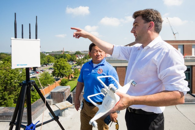 David Prantl (right), Dedrone's vice president of technology, holds a DJI Phantom 4 drone while discussing the newly installed Dedrone RF-100 drone-detection device with Vihn Cayton, antiterrorism officer, Joint Base Myer-Henderson Hall Directorate of Plans, Training, Mobilization and Security on the roof of Fort Lesley J. McNair's Marshall Hall July 19.