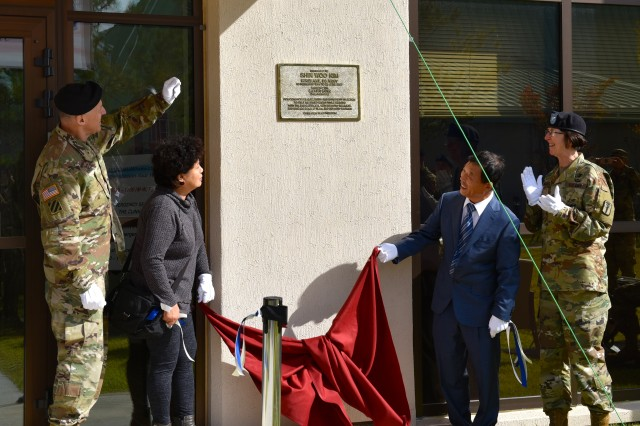 Eighth United States Army Commanding General, Lt. Gen. Thomas Vandal and 65th Medical Brigade Commander, Col. Wendy Harter assist the parents of Sgt. Shin Woo Kim to unveil the memorialization plaque naming the newest medical facility on U.S. Army Garrison Humphreys as the Sgt. Shin Woo Kim Soldier Center Medical Home and Dental Clinic.
