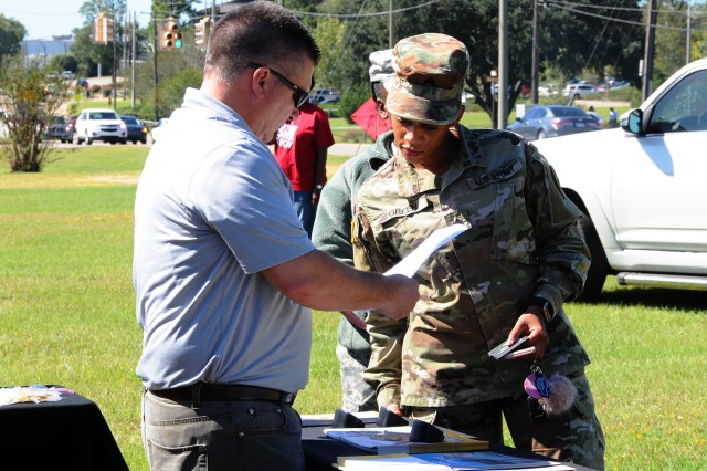 Sgt. Toni Green, 1st Battalion, 145th Aviation Regiment, speaks with school representatives during the Fall Education Fair Oct. 20.