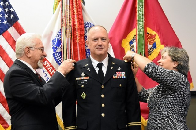 Chaplain (Lt. Col.) Byrd's father-in-law, Dr. Eliu Camacho, who is a retired Army officer, and Byrd's wife, Dorcas, pin on his new Lieutenant Colonel rank during his promotion ceremony held at Joint Munitions Command Headquarters.  (Photo by Nathan Joyce, JMC Public and Congressional Affairs.)