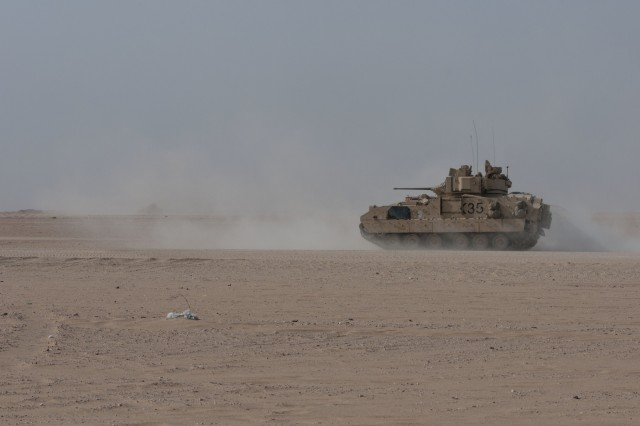 A Bradley Fighting Vehicle with C Company, 1st Battalion, 12th Cavalry Regiment, charges forward during a training exercise on Udari Range Complex near Camp Buehring, Kuwait, Oct. 17, 2017. The infantry unit conducted a platoon mounted and dismounted assault on an objective, an exercise that better prepares it to certify for future deployments after it returns to the U.S.