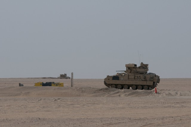 Two Bradley Fighting Vehicles with C Company, 1st Battalion, 12th Cavalry Regiment, simulate engaging targets during a training exercise on Udari Range Complex near Camp Buehring, Kuwait, Oct. 17, 2017. The infantry unit conducted a platoon mounted and dismounted assault on an objective, an exercise that better prepares it to certify for future deployments after it returns to the U.S.