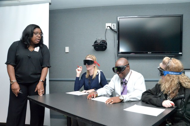 Wanda Gilbert, Employee Assistance Program coordinator with Redstone Arsenal, leads three employees of the U.S. Army Engineering and Support Center, Huntsville, through a navigation exercise Oct. 24, 2017, with goggles that simulate alcohol and/or drug intoxication. Beside Gilbert are, from left, Kristal Huinker, project management specialist with the Medical Repair and Renewal Program; Christopher Barnett, lead contract specialist with Information Technology Systems; and Shannon Robbins, international administrative assistant with Ordnance and Explosives. Gilbert's training also included a class on suicide awareness and prevention.