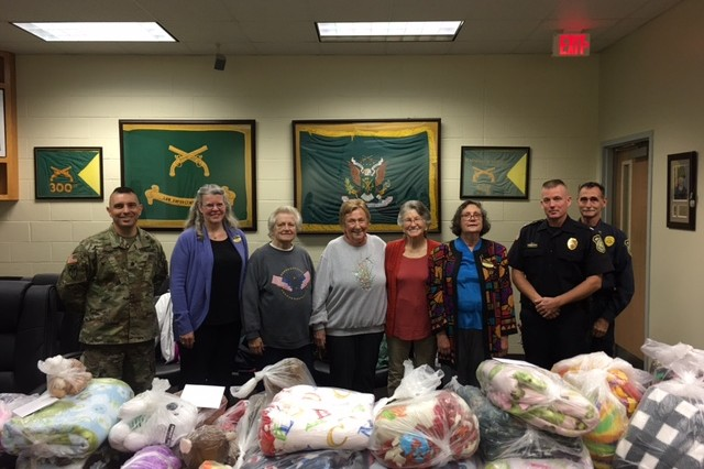 Members of the SOS Coffee Group donate blankets and stuffed animals to FLW DES