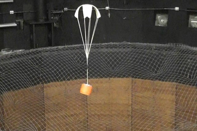 The Natick Soldier Research, Development and Engineering Center, or NSRDEC, is working with the Armament Research, Development and Engineering Center, or ARDEC, on special purpose parachutes for use with artillery projectiles. Here a version of a cross parachute featuring high-strength para-aramid materials that resulted from the collaboration is tested in a vertical wind tunnel.