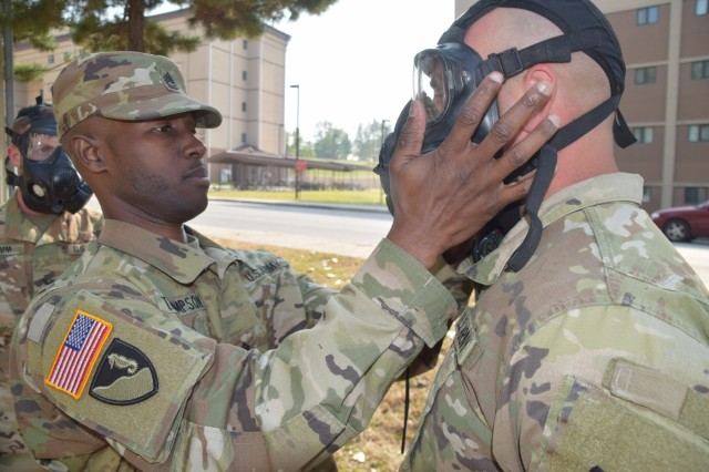 Sgt. 1st Class Jarvas Thompson, HHB, 35th ADA Brigade, tests Pfc. Luis Rivera's, 6-52 Air Defense Artillery Battalion, protective mask's seal during the chemical, biological, radiological and nuclear lane of the 35th ADA Brigade Missile Defender of the Year competition Oct. 25, 2017 at Osan Air Base, South Korea. Every fall, the top air defense crews from the Korean Peninsula compete in a series of events to claim the title of Missile Defender of the Year.