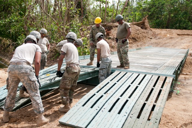 Soldiers with the 892nd Multi-Role Bridge Company, 190th Engineer Battalion from Juncos, Puerto Rico, lay a section of a ramp on a 40-foot bridge they are building for the citizens of Quebradillas, Puerto Rico, October 27. The 40-foot bridge will provide the municipalities of Quebradillas, San Sebastian, and Isabela, Puerto Rico, with a functional bridge until the bridges around the Guajataca Dam, which were destroyed by Hurricane Maria, are repaired.