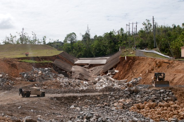 A damaged road near Quebradillas, Puerto Rico, October 27. Soldiers from the 892nd Multi-Role Bridge Company, 190th Engineer Battalion are constructing a 40-foot bridge for the citizens of the area until the bridges around the Guajataca Dam, which were destroyed by Hurricane Maria, are repaired.