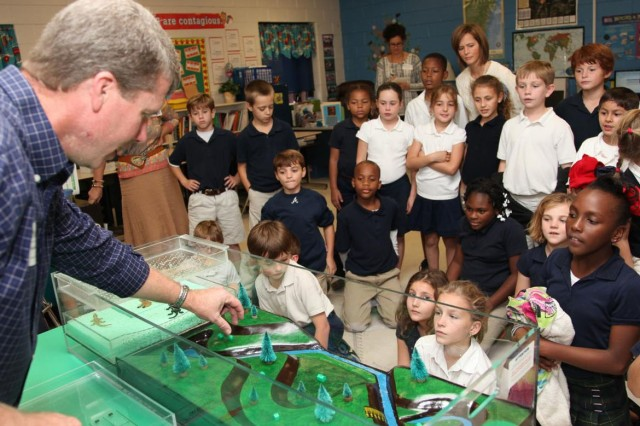 Regulatory Specialist Brian Moore uses an interactive floodplain model to demonstrate how wetlands absorb storm water and filter drinking water to a class of third grade students at Marshpoint Elementary School, Nov.5, 2013.