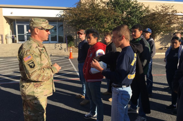 """USAOTC's Command Sgt. Maj. Mario O. Terenas, talks with a platoon of Copperas Cove ISD JROTC Cadets, who joined the command for """"Make A Difference Day"""" at Florence ISD school campuses."""