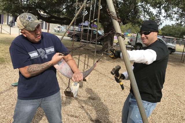 """Aurelio Luna (left), spouse of a USAOTC Army Civilian employee, joins Maj. Peter Moore, a test officer with USAOTC's Mission Command Test Directorate, in mending swing set chains at the Florence ISD Elementary School playground on """"Make A Difference Day."""""""
