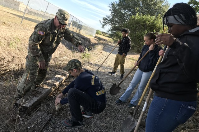 """USAOTC's Command Sgt. Maj. Mario O. Terenas, provides some direction to Copperas Cove ISD JROTC Cadets, while repairing a running trail at Florence ISD's High School on """"Make A Difference Day."""""""