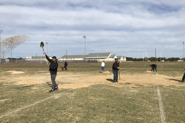 """Johnathan Sanchez (left), a senior with the Copperas Cove ISD JROTC program, tosses a shovel of sand on a sports field at Florence ISD High School while he volunteers his time on """"Make A Difference Day."""""""