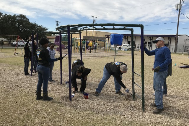 """Soldiers and Army Civilians with U.S. Army Operational Test Command paint monkey bars on """"Make A Difference Day"""" at the Florence ISD Elementary School playground."""